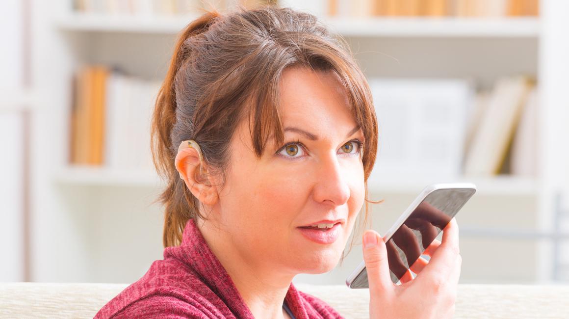 Mujer con audífonos hablando utilizando apps en en su dispositivo telefónico
