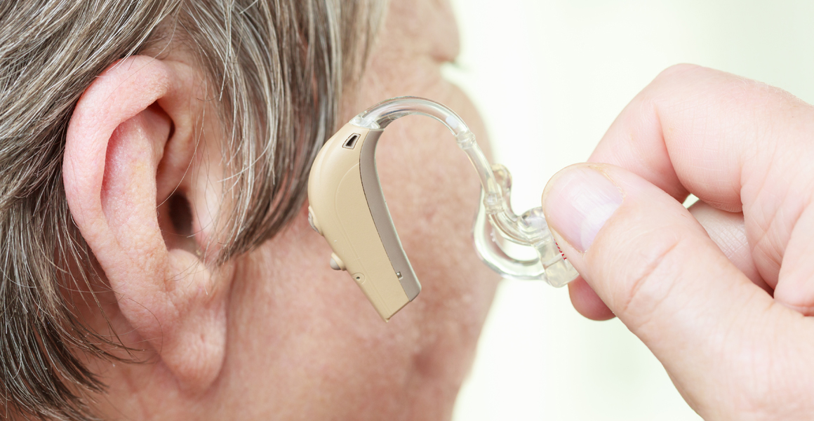 Adult woman putting on a hearing aid - Professionals
