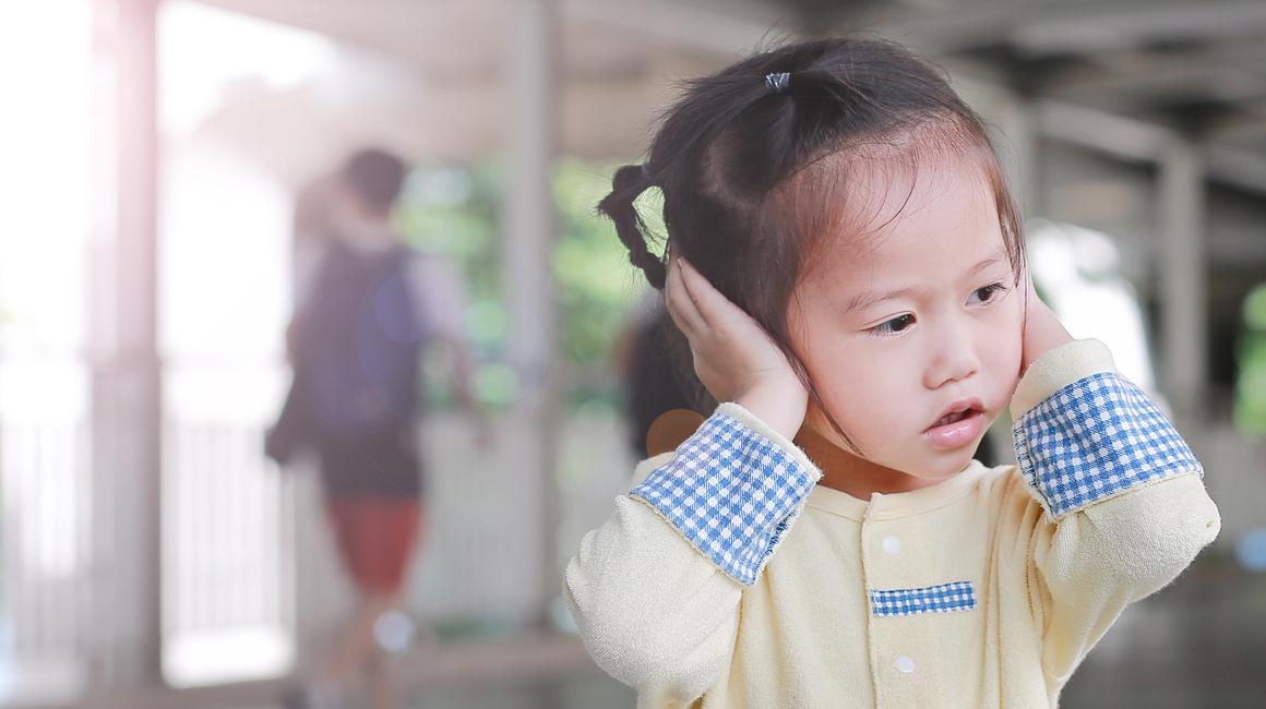 Niña tapándose los oídos en un centro educativo - Educación